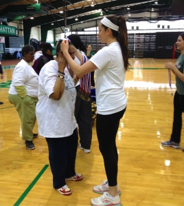A participant is awarded an award during the Manhattan College Games.
